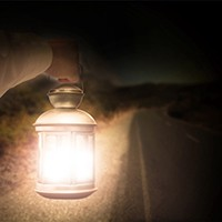 Hand holding light illuminating dark road at night