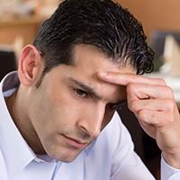 Verzweifelter Mann stützt seinen Kopf